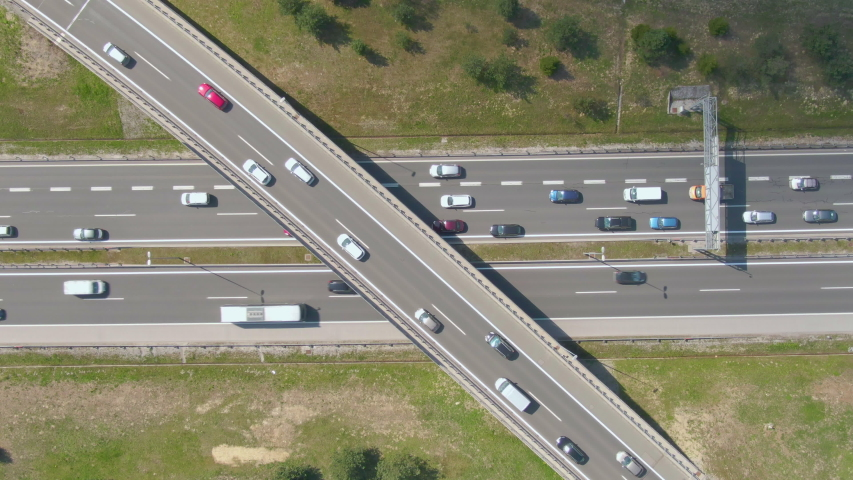 DRONE, TOP DOWN: Flying above a busy overpass and highway full of cars during rush hour. New highway network is full of tourists and commuters on a sunny day. Congested traffic in peak commute hours | Shutterstock HD Video #1031308190