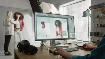Professional Photographer Sitting at His Desk Uses Desktop Computer in a Photo Studio Retouches. After Photoshoot He Retouches Photographs of Beautiful Black Female Model in an Image Editing Software