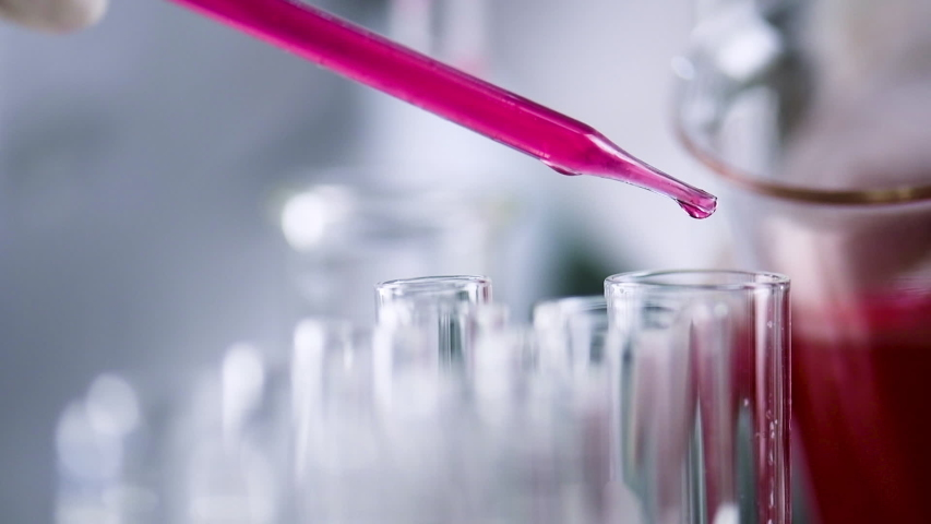 Scientist  hand holding a medical dropper filled with red solution dripping  chemical liquid sample to flask test tube in the genetic laboratory. Science laboratory test tubes , laboratory equipment  | Shutterstock HD Video #1031485730
