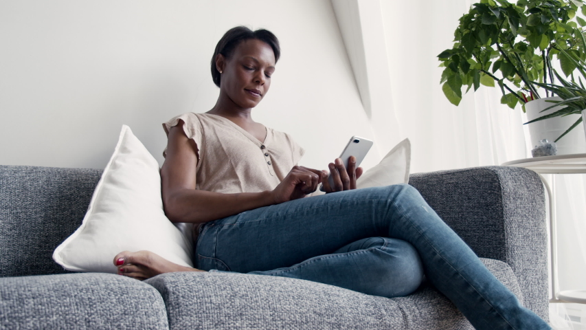 Solitary woman using mobile phone at home | Shutterstock HD Video #1031498810