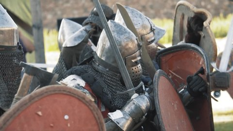 Medieval knight battle. Warriors in full plate armor with melee weapons. Armed men fighting. Real historical warfare reenactment