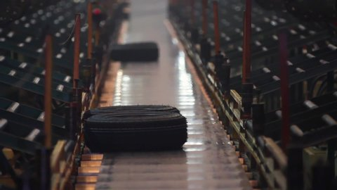 Process of forming tires in a factory. Manufacture of tires. Tyre production machine conveyor. Process of forming tires in a factory. Hot, smoked tires after molding arrive on the conveyor.