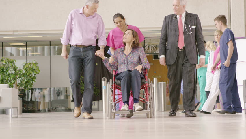 4K Caring medical staff in modern hospital help a patient in a wheelchair to stand | Shutterstock HD Video #10316252