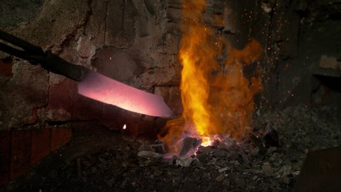 SLOW MOTION CLOSE UP, DOF: Blacksmith pulls a glowing knife blade out of the fire blazing in the furnace. Unrecognizable person forging a blade pulls the heated piece of metal out of the burning ember