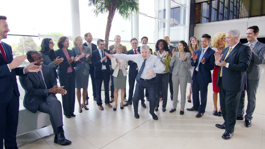 4K Self confident businessman doing funny dancing to entertain his colleagues