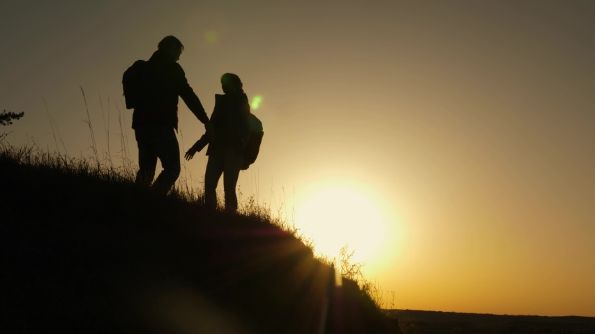 Travelers man and woman rejoice and dance at top of mountain. travelers climb the cliff holding hands. teamwork of business people. Happy family on vacation. tourists hug on top of mountain | Shutterstock HD Video #1031690330