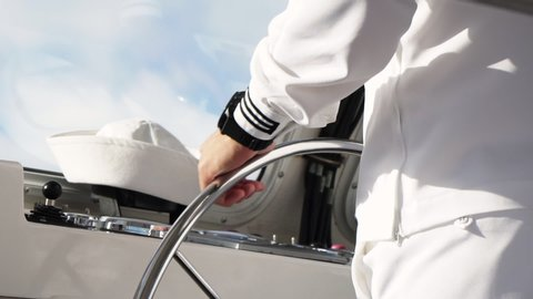 Sailor's hands at the helm in slow motion, with a white beret on the  instrument panel