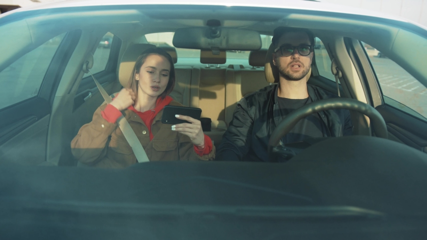 Young attractive couple sitting in auto, starting car. Girl with smartphone in hands using navigator app, showing way to boyfriend. Destination. Strange city. Outdoors. | Shutterstock HD Video #1031742740