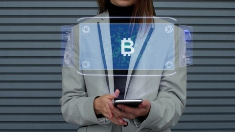 Unrecognizable business woman, interacts with a HUD hologram with text Sign BTC. Girl in a business suit uses the technology of the future mobile screen against the background of a striped wall