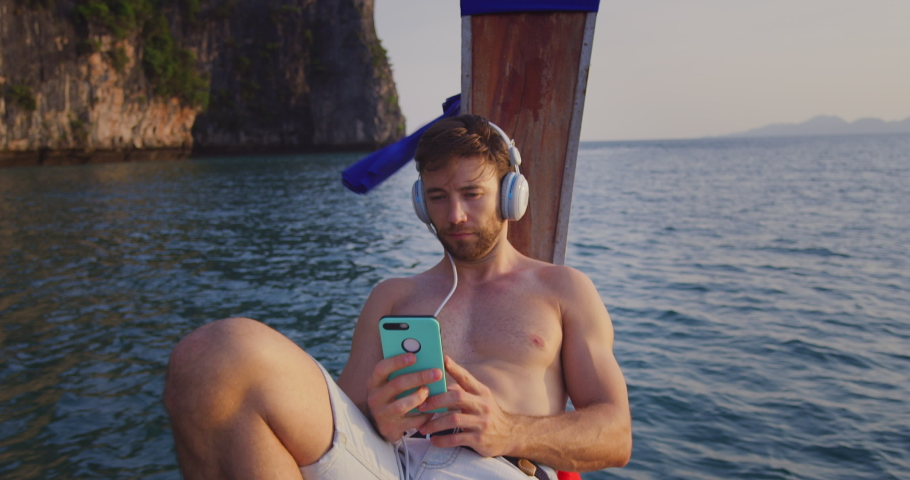 Man listening to music on smartphone with headset on long tail boat tour in Asia Thailand, with lime stone cliffs in South East Asia at sunset. Slow motion hand held. Shot on red. | Shutterstock HD Video #1031857820