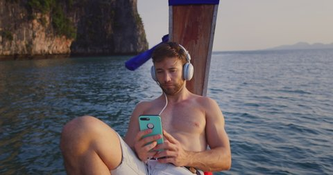 Man listening to music on smartphone with headset on long tail boat tour in Asia Thailand, with lime stone cliffs in South East Asia at sunset. Slow motion hand held. Shot on red.