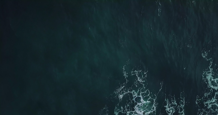 Timelapse. Aerial top view waves break on rocks in a blue ocean. Sea waves on beautiful beach aerial view drone 4k shot. Bird's eye view of ocean waves crashing against an empty stone from above. | Shutterstock HD Video #1031874680