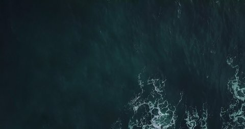 Timelapse. Aerial top view waves break on rocks in a blue ocean. Sea waves on beautiful beach aerial view drone 4k shot. Bird's eye view of ocean waves crashing against an empty stone from above.