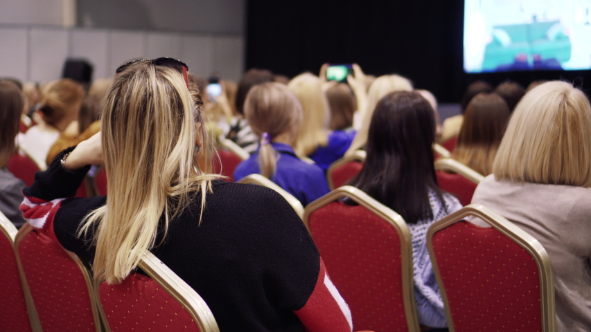 A female audience listens to a lecture and presentation in a large hall. Businesswomans seat in auditorium and watch workshop. Professional ideas, politics or economy. Back view.   Shutterstock HD Video #1031877050