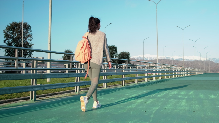 Cheerful young schoolgirl is going on training in stadium on open air. She is stepping over special soft cover for runners, back view #1031877410