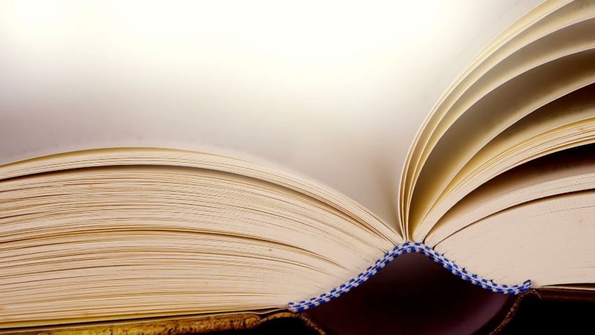 Close up opened book on the table , wind turning the book page ,reading textbook or  learning education concept    Shutterstock HD Video #1031891510