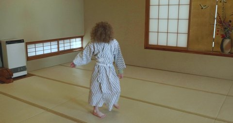 Small caucasian boy with long curly hair twists, twirls, dances and jumps on a Japanese tatami mat floor while wearing traditional yukata