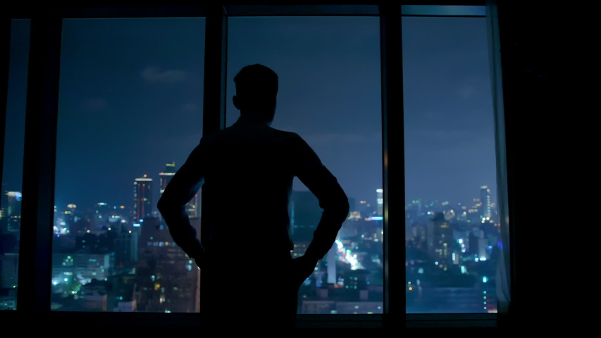 Silhouette of upset businessman watching through the window at night | Shutterstock HD Video #1031954300