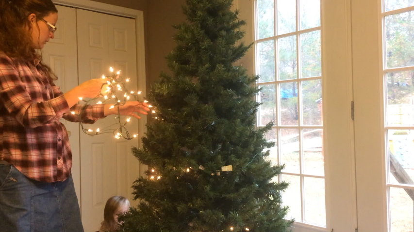 Mother and daughter decorating Christmas tree together   Shutterstock HD Video #1031975990