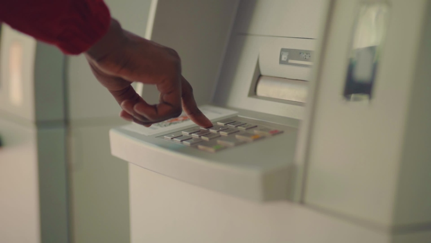 Close up of Afro-American businessman entering his pin code on keyboard of ATM, banking service, finance and people concept. Transfer, cash withdrawal. Soft selective focus | Shutterstock HD Video #1031980100