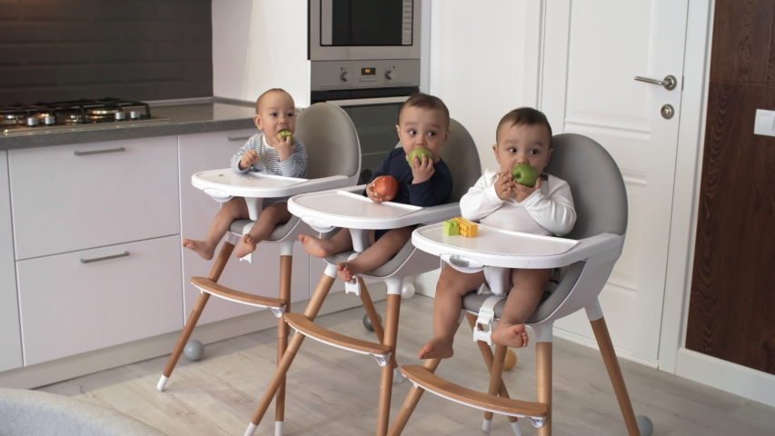 Full shot of 1-year-old Asian triplets, dressed in bodysuits, sitting in high chairs in kitchen, nibbling on green apples and looking towards something attentively | Shutterstock HD Video #1031991380