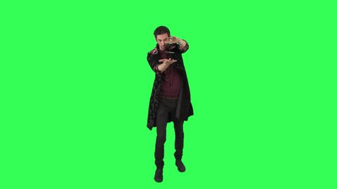 A magician performs a magic trick of a flying and spinning card over a green screen. Real footage, no post production effect.