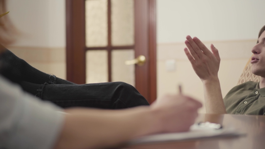 Relaxed young man sitting in office of psychologist with his feet on the table, telling her about his problems. Female psychologist consulting patient, writes notes in notebook | Shutterstock HD Video #1032078650