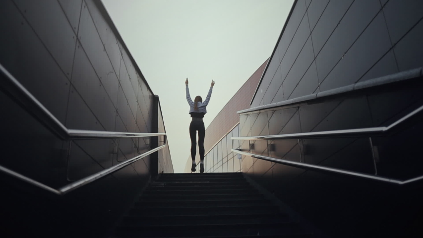 Young sporty woman running upstairs on city stairs. Concept of the winner. Slow motion   Shutterstock HD Video #1032147710