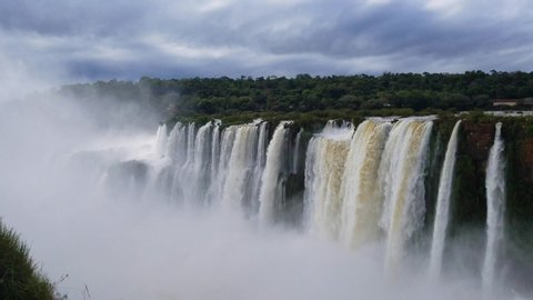 The beautiful Iguazu Falls on the border of Brazil and Argentina from the Argentina side on a cloudy day with mist from the falls rising.