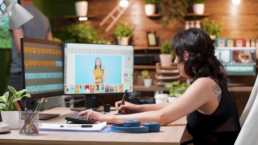 Female photographer edits photos in creative media agency office. In the background - a man is working on other projects on the computer | Shutterstock HD Video #1032326360