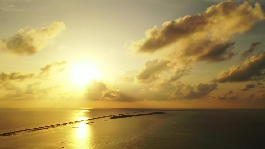 A dramatic golden sky during sunset. Beautiful clouds above the sea. Flight sideways. Truck left   Shutterstock HD Video #1032383390