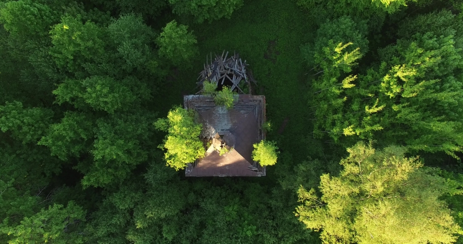 4K high quality early summer sunny afternoon aerial video footage of abandoned village site with ruins of old vintage church in the middle of dense green wild woods in Russia's Yaroslavl region