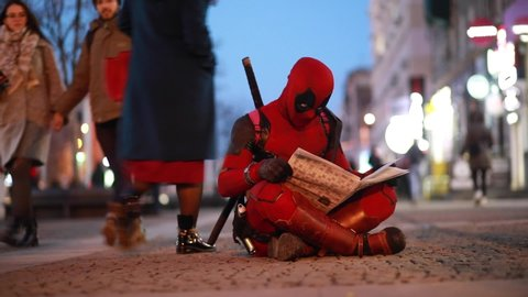 DNIPRO, UKRAINE - MARCH 28, 2019: Deadpool cosplayer sits on the sidewalk and reads newspaper in his hands on background of city street.