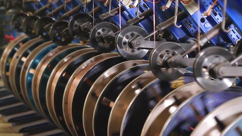 Steel wire coils at a tire factory. Rotating and reeling metal threads bobbins long line at modern tire production plant. Bronze wire is fed for the manufacture of the side rings of automotive wheels.