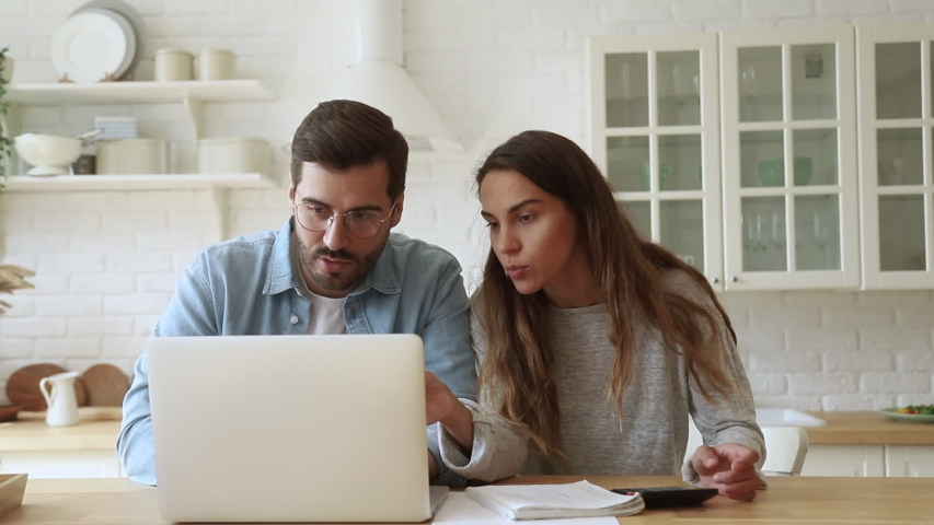 Serious young couple husband and wife pay bills online on website app doing paperwork planning budget discuss finances calculate mortgage payments using laptop computer sit at kitchen table at home | Shutterstock HD Video #1032517250