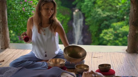 Superslowmotion shot of a woman master of Asian sacred medicine performs Tibetan bowls healing ritual for a client young woman. Meditation with Tibetan singing bowls. They are in a gazebo