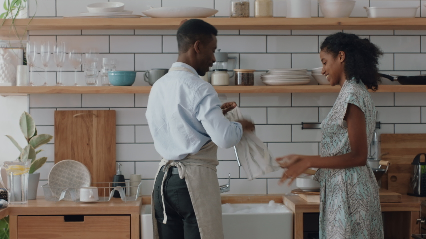Happy young mixed race couple washing dishes playing in kitchen having fun throwing soap bubbles enjoying romantic relationship playfully doing household chores 4k footage | Shutterstock HD Video #1032532340