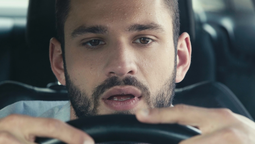 Close up of sweaty man gesturing while sitting in car and holding steering wheel | Shutterstock HD Video #1032683270
