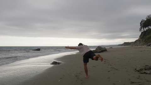 A fit man doing a yoga pose balancing in slow motion on a sandy beach with ocean waves in Santa Barbara, California.