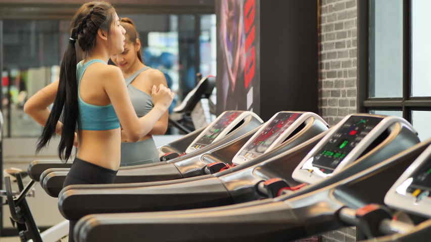 Young beautiful woman asian running on a treadmill and trainer helped guide at gym. Fitness and healthy lifestyle concept. Side view of girl in sportswear jogging exercise. Slow motion | Shutterstock HD Video #1032817100