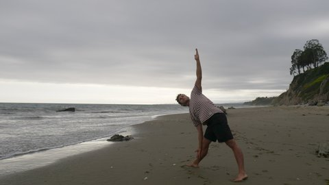 A man doing yoga on the beach for stress relief with ocean waves in California SLOW MOTION.