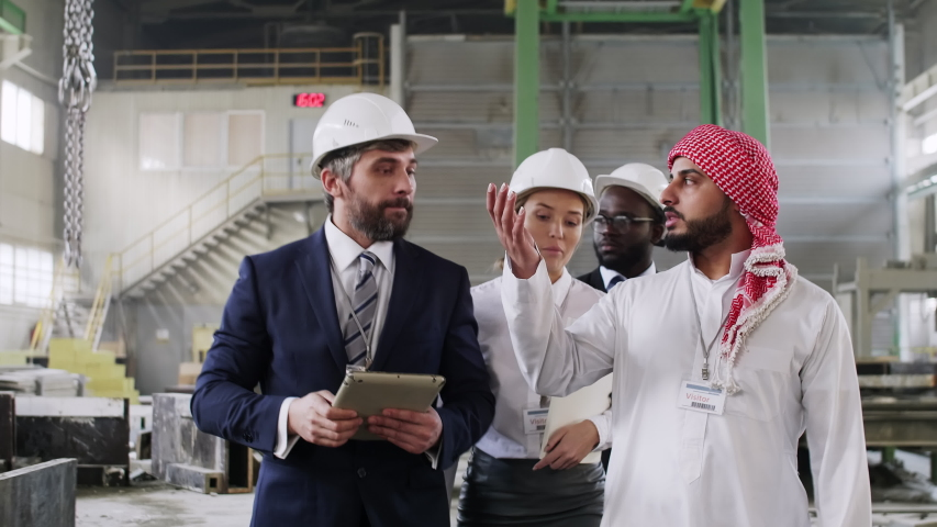 Tilt up shot of Caucasian engineers welcoming international colleagues at factory and giving an excursion | Shutterstock HD Video #1032909230