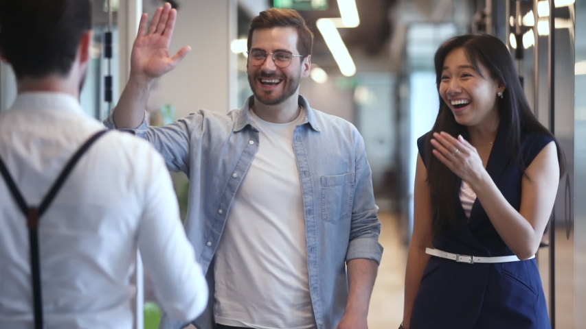 Happy diverse colleagues greeting talking standing in office hall, smiling multiethnic staff professional people giving high five chatting laughing enjoy friendly conversation meeting in work space | Shutterstock HD Video #1032911180