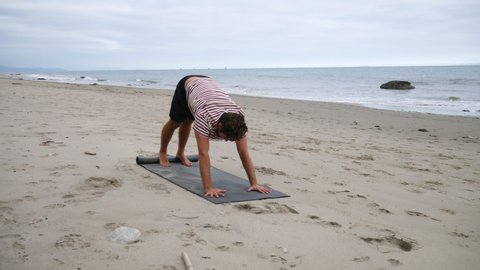 A man stretching and doing yoga on an overcast sand beach with ocean waves SLOW MOTION.