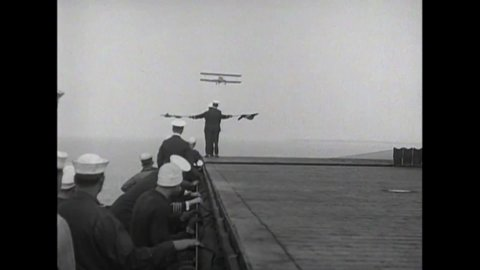 Circa 1924 - slow motion is used to show biplanes landing smoothly on the  uss langley