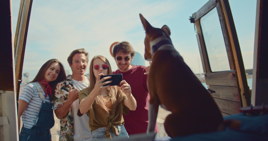 Group of happy friends traveling with puppy dog on camper van making selfie together on smartphone posing with positive emotions, smiling woman hugging her boyfriend, Summertime Adventure Road Trip | Shutterstock HD Video #1032989270
