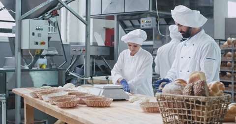 Baking industry three professional bakers working concentrated with dough they prepare for baking the bread , stylish dress code. shot on red epic