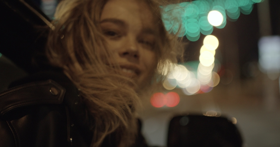Young pretty girl in car, leans out passenger side car window, wind stirs her hair, she looks at the night city, night road, girl looking at the camera. | Shutterstock HD Video #1033025270