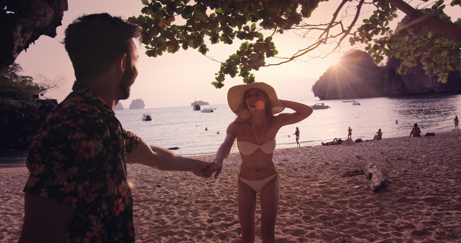 Young travel couple holding hands, woman leading boyfriend. while on Railay Beach at sunset with sun flare. Slow motion, hand held, pov travel concept. Shot on red.