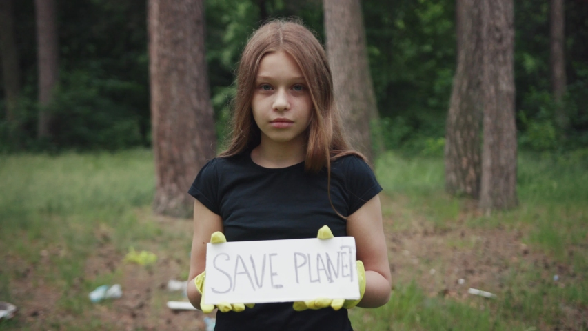 Save Earth concept. Pretty girl holding a sign protesting against plastic use. Young volunteer striking for ecology and clean planet.   Shutterstock HD Video #1033090190
